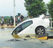 路面沉降突然出现大水坑 小车中招一头栽了进去